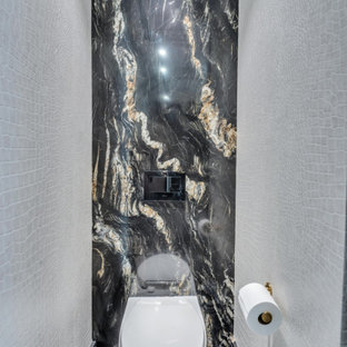 Inspiration for an expansive shabby-chic style powder room in New York with furniture-like cabinets, black cabinets, a wall-mount toilet, black tile, marble, beige walls, marble floors, a wall-mount sink, quartzite benchtops, black floor, black benchtops and a floating vanity.