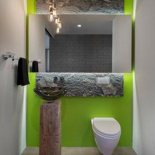 Imagen de aseo actual, pequeño, con lavabo sobreencimera, sanitario de pared, paredes verdes, suelo de cemento, puertas de armario con efecto envejecido, baldosas y/o azulejos de mármol y suelo gris