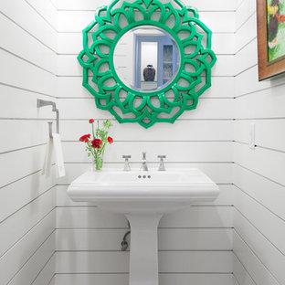 Ejemplo de aseo costero, pequeño, con lavabo con pedestal, paredes blancas y suelo de travertino