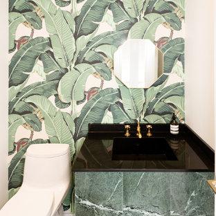 Réalisation d'un petit WC et toilettes nordique avec un placard à porte plane, des portes de placards vertess, un mur vert, un lavabo encastré, un plan de toilette en marbre et un plan de toilette noir.