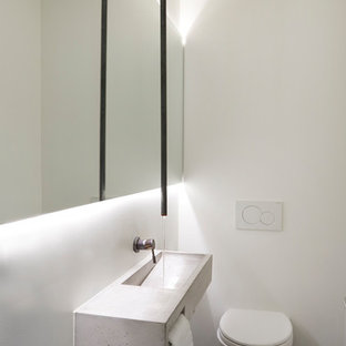 Inspiration for a small contemporary cloakroom in Toronto with a wall mounted toilet, white walls, slate flooring, an integrated sink and concrete worktops.