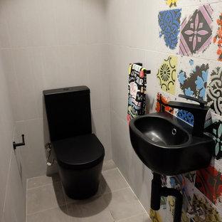 Foto de aseo actual, pequeño, con sanitario de dos piezas, baldosas y/o azulejos multicolor, baldosas y/o azulejos de porcelana, lavabo suspendido, paredes grises, suelo gris y encimeras negras