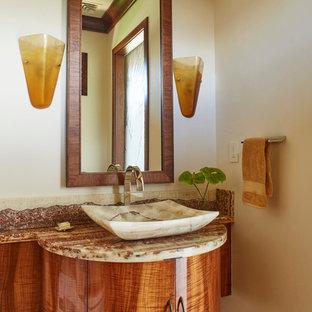 ハワイの広いトロピカルスタイルのおしゃれなトイレ・洗面所 (家具調キャビネット、濃色木目調キャビネット、御影石の洗面台、石スラブタイル、マルチカラーの壁、トラバーチンの床、ベッセル式洗面器) の写真