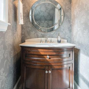 Kleine Klassische Gästetoilette mit Schrankfronten im Shaker-Stil, braunen Schränken, Wandtoilette mit Spülkasten, grauen Fliesen, grauer Wandfarbe, Mosaik-Bodenfliesen, Unterbauwaschbecken, Quarzwerkstein-Waschtisch, grauem Boden und weißer Waschtischplatte in Houston