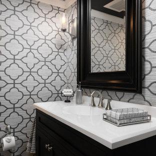 На фото: маленький туалет в классическом стиле с плоскими фасадами, черными фасадами, раздельным унитазом, серыми стенами, светлым паркетным полом, монолитной раковиной, столешницей из искусственного камня, бежевым полом, белой столешницей, напольной тумбой и обоями на стенах с