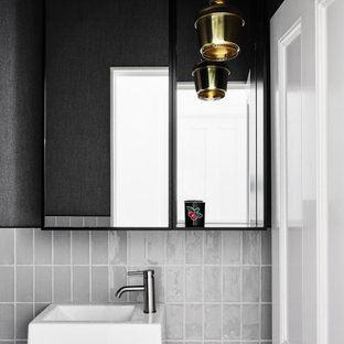 Photo of a contemporary powder room in Melbourne with gray tile, black walls and a wall-mount sink.