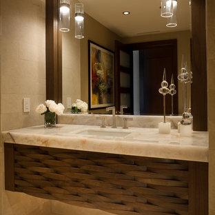 На фото: туалеты среднего размера в современном стиле с коричневыми фасадами, бежевой плиткой, плиткой из известняка, бежевыми стенами, полом из известняка, врезной раковиной, столешницей из кварцита и бежевым полом
