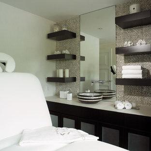 Exemple d'un WC et toilettes chic de taille moyenne avec un placard à porte plane, des portes de placard noires, un carrelage beige, une plaque de galets, un mur beige, une vasque, un plan de toilette en surface solide et un plan de toilette blanc.