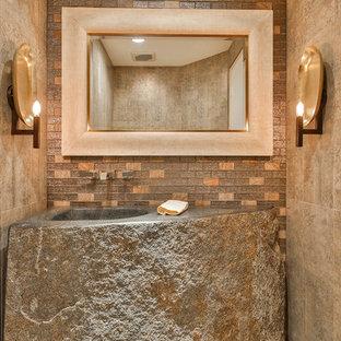 Réalisation d'un WC et toilettes chalet de taille moyenne avec un carrelage beige, des carreaux de céramique, un mur beige, un sol en carreaux de ciment, un lavabo intégré, un plan de toilette en calcaire et un sol gris.
