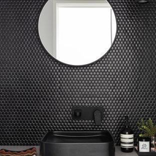 На фото: туалеты в стиле лофт с фасадами цвета дерева среднего тона, черной плиткой, плиткой мозаикой, полом из цементной плитки, настольной раковиной, столешницей из искусственного кварца, черным полом и серой столешницей