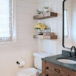 小さいインダストリアルスタイルのおしゃれなトイレ・洗面所 (ヴィンテージ仕上げキャビネット、分離型トイレ、セラミックタイルの床、アンダーカウンター洗面器、ソープストーンの洗面台、グレーの床、白い壁) の写真