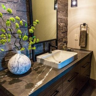 Идея дизайна: большой туалет в стиле модернизм с плоскими фасадами, темными деревянными фасадами, раздельным унитазом, черно-белой плиткой, каменной плиткой, бежевыми стенами, полом из керамогранита, накладной раковиной, мраморной столешницей, серым полом и черной столешницей
