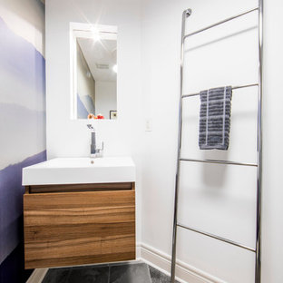 Medium sized modern cloakroom in Toronto with flat-panel cabinets, medium wood cabinets, a one-piece toilet, white walls, slate flooring, an integrated sink, engineered stone worktops, grey floors and white worktops.