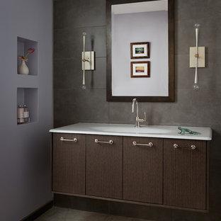 Inspiration pour des WC et toilettes minimalistes de taille moyenne avec un placard à porte plane, des portes de placard en bois sombre, un carrelage gris, des carreaux de porcelaine, un mur violet et un sol en calcaire.