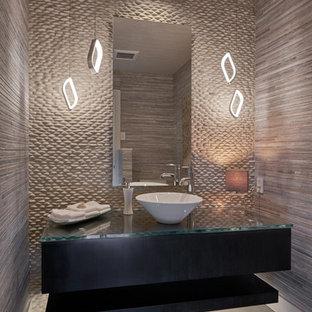 Idées déco pour un WC et toilettes contemporain de taille moyenne avec un placard sans porte, des portes de placard en bois sombre, un carrelage beige, un carrelage de pierre, un mur beige, béton au sol, une vasque et un plan de toilette en verre.
