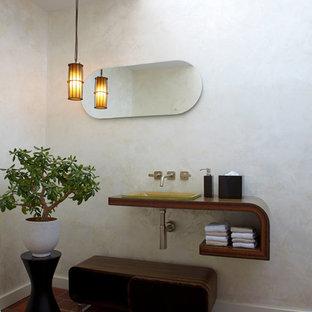 Idee per un bagno di servizio etnico con top in legno, pavimento in terracotta, lavabo da incasso e top marrone