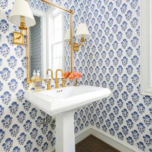 Idée de décoration pour un WC et toilettes tradition avec un mur bleu, un sol en bois foncé, un plan vasque et un sol marron.