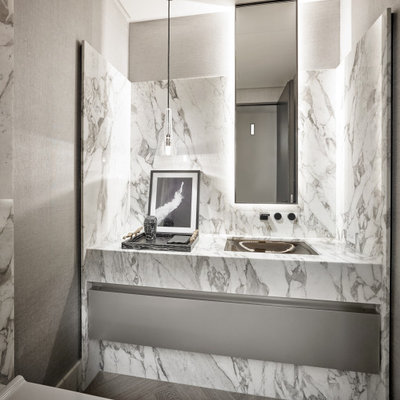 Example of a trendy white tile dark wood floor and brown floor powder room design in Miami with flat-panel cabinets, gray cabinets, gray walls, an undermount sink, white countertops and a floating vanity
