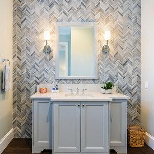 Inspiration pour un WC et toilettes rustique de taille moyenne avec un placard en trompe-l'oeil, des portes de placard grises, un carrelage gris, un carrelage de pierre, un mur gris, un sol en bois brun, un lavabo encastré, un plan de toilette en quartz modifié, un sol marron et un plan de toilette blanc.