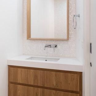 Idee per un ampio bagno di servizio costiero con ante con bugna sagomata, ante in legno scuro, WC monopezzo, piastrelle multicolore, piastrelle a mosaico, pareti bianche, pavimento in gres porcellanato, lavabo sottopiano, top in quarzo composito, pavimento beige e top bianco