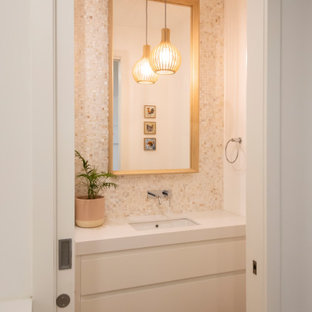Expansive beach style cloakroom in Melbourne with raised-panel cabinets, white cabinets, a one-piece toilet, multi-coloured tiles, mosaic tiles, white walls, medium hardwood flooring, a submerged sink, engineered stone worktops and white worktops.