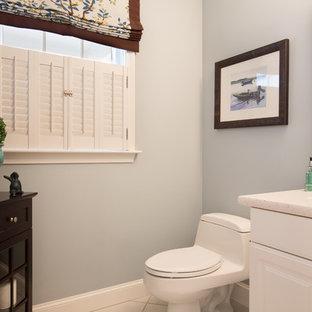 На фото: маленький туалет в стиле современная классика с фасадами с выступающей филенкой, белыми фасадами, унитазом-моноблоком, бежевой плиткой, синими стенами, полом из керамической плитки, консольной раковиной и столешницей из искусственного камня с