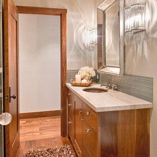 Immagine di un bagno di servizio chic con lavabo sottopiano, ante in stile shaker, ante in legno scuro, WC monopezzo, piastrelle di vetro e pareti grigie