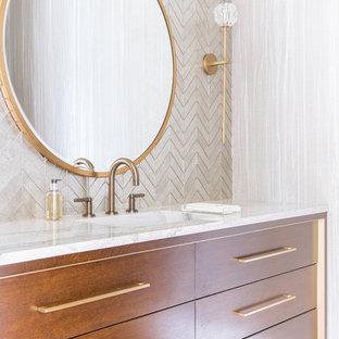 Réalisation d'un grand WC et toilettes méditerranéen avec un placard en trompe-l'oeil, des portes de placard marrons, un carrelage blanc, un mur beige, un sol en bois clair, un lavabo intégré, un plan de toilette en marbre et un plan de toilette blanc.