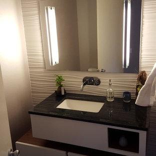 Réalisation d'un petit WC et toilettes minimaliste avec un placard en trompe-l'oeil, des portes de placard en bois brun, un WC à poser, un carrelage blanc, des carreaux de céramique, un mur gris, un sol en bois foncé, un lavabo encastré et un plan de toilette en verre.