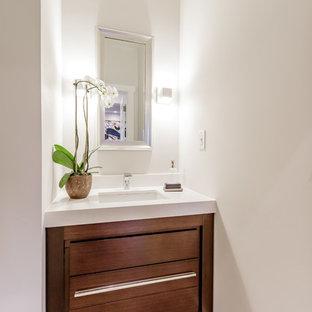 Modelo de aseo contemporáneo, pequeño, con armarios con paneles lisos, puertas de armario de madera oscura, sanitario de una pieza, baldosas y/o azulejos beige, baldosas y/o azulejos de cerámica, paredes blancas, suelo de baldosas de cerámica, lavabo integrado, encimera de cuarzo compacto y encimeras blancas