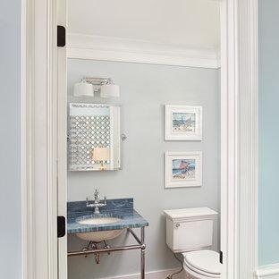 Idee per un bagno di servizio tropicale con lavabo sottopiano e top blu
