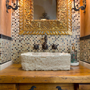 Идея дизайна: маленький туалет в средиземноморском стиле с каменной плиткой, настольной раковиной, столешницей из дерева, фасадами островного типа, фасадами цвета дерева среднего тона, оранжевыми стенами и коричневой столешницей