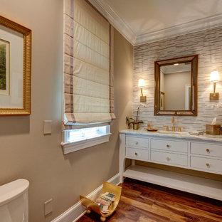 Пример оригинального дизайна: большой туалет в стиле современная классика с фасадами островного типа, белыми фасадами, белой плиткой, бежевой плиткой, бежевыми стенами, темным паркетным полом, врезной раковиной, мраморной столешницей и удлиненной плиткой