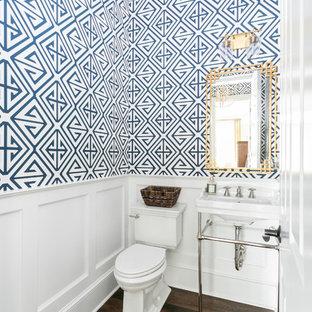 Cette photo montre un WC et toilettes bord de mer avec un WC séparé, un mur bleu, un sol en bois foncé, un plan vasque et un sol marron.