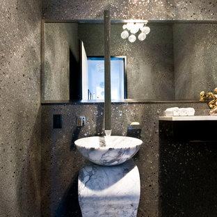 На фото: маленький туалет в современном стиле с раковиной с пьедесталом, плоскими фасадами, темными деревянными фасадами, унитазом-моноблоком, серой плиткой и серыми стенами с
