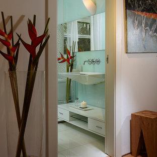 マイアミの中くらいのモダンスタイルのおしゃれなトイレ・洗面所 (壁付け型シンク、オープンシェルフ、白いキャビネット、一体型トイレ、白いタイル、ガラス板タイル、白い壁) の写真