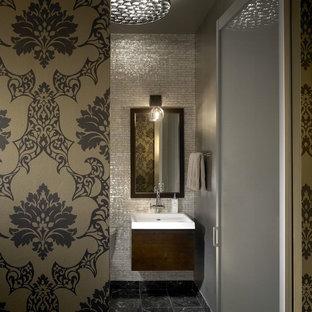 Aménagement d'un WC et toilettes industriel avec un lavabo suspendu, des portes de placard en bois sombre et un carrelage gris.