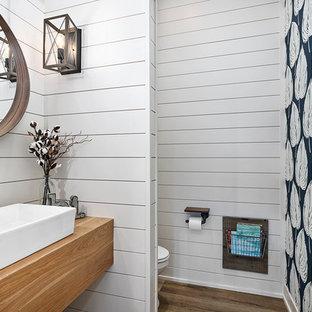 Пример оригинального дизайна: туалет в стиле кантри с открытыми фасадами, фасадами цвета дерева среднего тона, раздельным унитазом, белыми стенами, полом из винила, настольной раковиной, столешницей из дерева, коричневым полом и коричневой столешницей