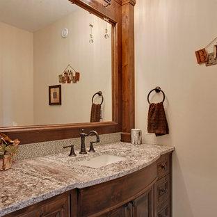 カルガリーの中サイズのラスティックスタイルのおしゃれなトイレ・洗面所 (アンダーカウンター洗面器、レイズドパネル扉のキャビネット、濃色木目調キャビネット、御影石の洗面台、ベージュのタイル、ガラスタイル、ベージュの壁) の写真