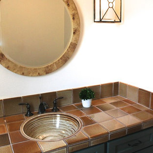 This is an example of a small bohemian cloakroom in San Francisco with shaker cabinets, green cabinets, a one-piece toilet, multi-coloured tiles, ceramic tiles, beige walls, dark hardwood flooring, a built-in sink and tiled worktops.
