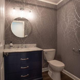 他の地域の小さいトランジショナルスタイルのおしゃれなトイレ・洗面所 (青いキャビネット、分離型トイレ、グレーの壁、無垢フローリング、アンダーカウンター洗面器、大理石の洗面台、マルチカラーの床、白い洗面カウンター、独立型洗面台、折り上げ天井、壁紙) の写真
