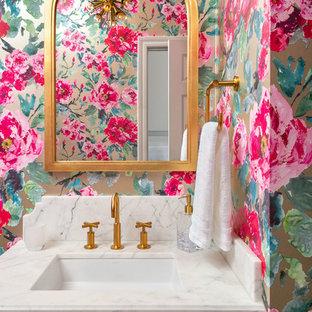 Réalisation d'un WC et toilettes tradition avec un placard avec porte à panneau surélevé, des portes de placard bleues, un mur multicolore, un lavabo encastré et un plan de toilette blanc.