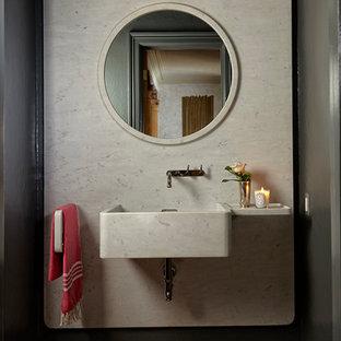 Idées déco pour un WC et toilettes méditerranéen avec un carrelage blanc, un mur gris, un sol en bois brun, un lavabo suspendu, un sol marron et un plan de toilette blanc.