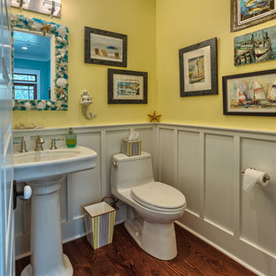 Photo of a beach style cloakroom in New Orleans with yellow walls, dark hardwood flooring, a pedestal sink and brown floors.