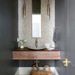 Cette photo montre un WC et toilettes chic avec un carrelage beige, un mur noir, un sol en bois clair et une vasque.