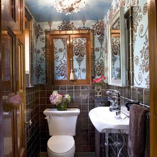 Modelo de aseo tradicional, pequeño, con lavabo suspendido, baldosas y/o azulejos marrones, sanitario de dos piezas, paredes azules y suelo de terrazo