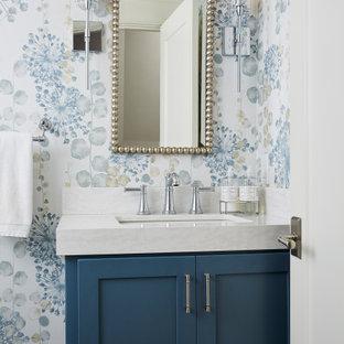 Aménagement d'un WC et toilettes classique de taille moyenne avec un placard avec porte à panneau encastré, des portes de placard bleues, un WC séparé, un mur bleu, un lavabo encastré, un plan de toilette en quartz et un plan de toilette blanc.