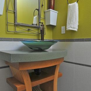 Idee per un bagno di servizio minimal con lavabo a bacinella, top in cemento e top verde