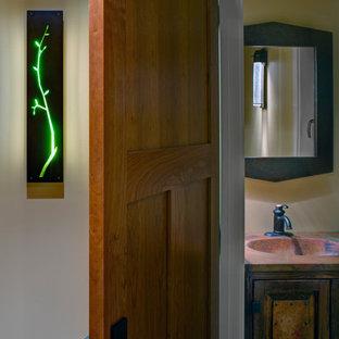 ボルチモアの小さいラスティックスタイルのおしゃれなトイレ・洗面所 (レイズドパネル扉のキャビネット、ヴィンテージ仕上げキャビネット、分離型トイレ、黄色い壁、オーバーカウンターシンク、人工大理石カウンター、マルチカラーの洗面カウンター) の写真