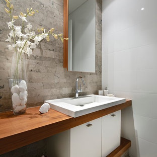 パースの小さいコンテンポラリースタイルのおしゃれなトイレ・洗面所 (オーバーカウンターシンク、フラットパネル扉のキャビネット、白いキャビネット、木製洗面台、白い壁、ライムストーンの床、ライムストーンタイル、ブラウンの洗面カウンター) の写真